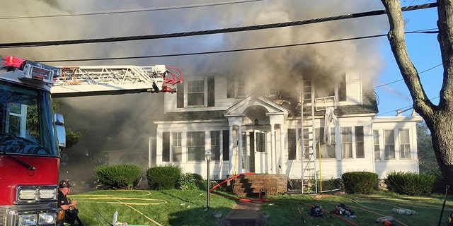 Firefighters battle a house fire on Thursday in North Andover, one of multiple emergency crews responding to a series of gas explosions and fires triggered by a problem with a gas line that feeds homes in several communities north of Boston.