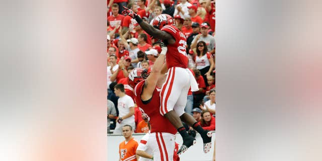 Wisconsin's Melvin Gordon is lifted by teammate Rob Havenstein after Gordon's 69-yard touchdown run during the second half of an NCAA college football game against Bowling Green, Saturday, Sept. 20, 2014, in Madison, Wis. (AP Photo/Morry Gash)