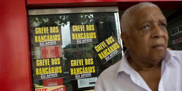 A man leaves the ATM of a striking bank, in Rio de Janeiro, Brazil, Wednesday, Oct. 5, 2016.