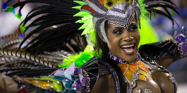 A performer from the Mocidade samba school parades during carnival celebrations at the Sambadrome in Rio de Janeiro, Brazil, Monday, March 3, 2014. Brazil's Carnival is maintaining its frenetic pace, with hundreds of roving parties taking over Rio de Janeiro's streets and famed samba school parades heading into their final night. (AP Photo/Felipe Dana)
