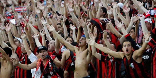 FILE - In this Nov.27, 2013 file photo, Atletico Paranaense fans cheer for their team during the Copa do Brazil  final match against Flamengo in Rio de Janeiro, Brazil. Brazilians fans idolize their stars on the fields, courts and tracks. They'll cheer loudly at any sporting event they'll go to, be it a World Cup match, a Formula One race or a mixed martial arts fight. (AP Photo/Victor R. Caivano, File)