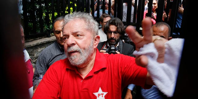 FILE - In this March 5, 2016 file photo, Brazil's former President Luiz Inacio Lula da Silva greets supporters who gathered outside his residence in Sao Bernardo do Campo, in the greater Sao Paulo area, Brazil. A Brazilian judge has ruled that Silva will stand trial on charges of money laundering and corruption. Judge Sergio Moro said Tuesday, Sept. 20, 2016 there is enough evidence to start a judicial process against Silva, his wife and six others in a widening corruption probe centered on the country's huge state-run oil company, Petrobras. (AP Photo/Andre Penner, File)