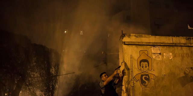 A Police officer of the Pacifying Police Unit, patrols among the smoke from burning barricades during clashes at the Pavao Pavaozinho slum in Rio de Janeiro, Brazil, Tuesday, April 22, 2014. Intense exchanges of gunfire, numerous blazes set alit and a shower of homemade explosives and glass bottles onto a busy avenue in Rio de Janeiros main tourist zone erupted Tuesday night after the death of a popular young shantytown resident. (AP Photo/Felipe Dana)