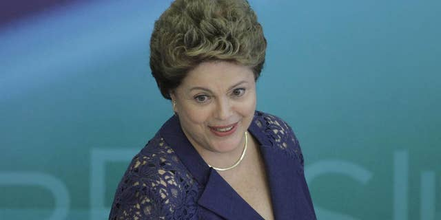 Brazil's President Dilma Rousseff arrives to attend a press conference at the Planalto Presidential Palace, in Brasilia, Brazil, Monday, Dec. 22, 2014. President Rousseff gave one of her last press conferences before the Christmas holiday and talked about various topics, including the recent Petrobras scandal. (AP Photo/Eraldo Peres)