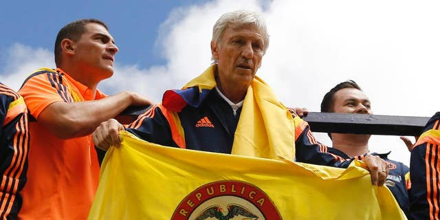 FILE - In this July 6, 2014 file photo, Colombia's coach Jose Pekerman, from Argentina, holds a Colombian flag as the team parades before supporters as they are welcomed home from the World Cup, in Bogota, Colombia, following their loss to Brazil in the quarterfinals. Colombia's Football Federation announced on Tuesday, Aug. 19, 2014 that Pekerman will stay on as coach for the national selection. (AP Photo/Fernando Vergara, File)