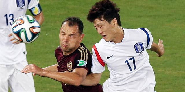 Russia's Sergei Ignashevich, left, and South Korea's Lee Chung-yong (17) go for a header during the group H World Cup soccer match between Russia and South Korea at the Arena Pantanal in Cuiaba, Brazil, Tuesday, June 17, 2014. (AP Photo/Thanassis Stavrakis)