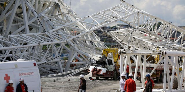 Nov. 27, 2013: People stand near a metal structure that buckled on part of the Itaquerao Stadium in Sao Paulo, Brazil.