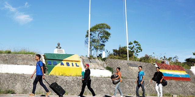 Venezuelans walk across the border into the Brazilian city of Pacaraima