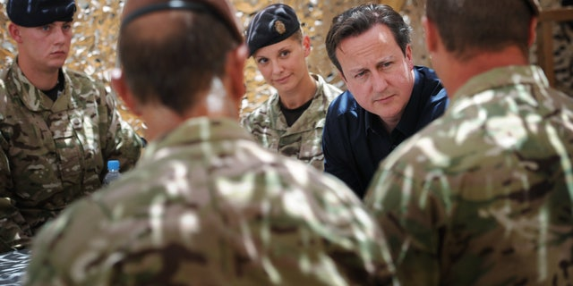 Britain's Prime Minister, David Cameron, has a drink and a chat with British soldiers (names not given) based at Lashkar Gah in Helmand Province, Afghanistan, Wednesday, July 18, 2012 during a surprise trip to the area. Earlier he met Afghan National Police chiefs. (AP Photo/Stefan Rousseau, Pool)