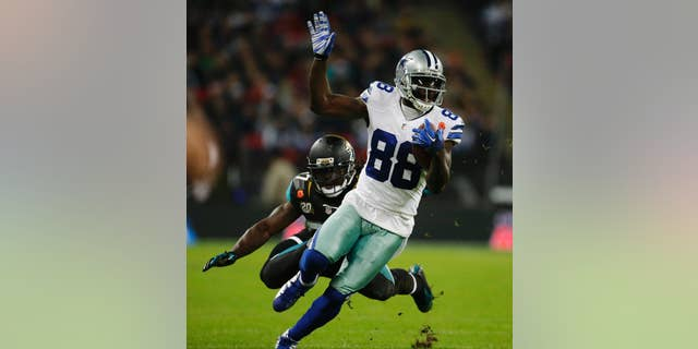 Dallas Cowboys wide receiver Dez Bryant (88) is defended by Jacksonville Jaguars strong safety Johnathan Cyprien (37) during the first half of an NFL football game at Wembley Stadium, London, Sunday, Nov. 9, 2014.  (AP Photo/Matt Dunham)