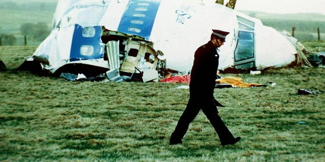 a police officer walks by the nose of Pan Am flight 103 in Lockerbie, Scotland, where it lay after a bomb aboard exploded, killing a total of 270 people.