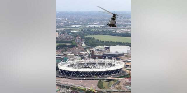 FILE - This is a Aug. 18, 2011 file photo released by Britain's Ministry of Defence  shows  Royal Air Force Puma helicopter is pictured flying over the 2012 Olympic Stadium during a training flight over London .  Fighter jets thunder above the English countryside. Missiles stand ready. And Big Brother is watching like never before. The London Olympics are no ordinary games _ and Britain is no ordinary host.  Not since World War II have Britain and the United States teamed up for such a massive security operation on British soil, and not without reason. (AP Photo/SAC Phil Major RAF, MOD)