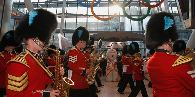 June 20, 2012: The Band of Irish Guards march pass a giant Olympic Rings unveiled at Heathrow airport Terminal 5 ready to welcome visitors to the London 2012 Olympic Games.