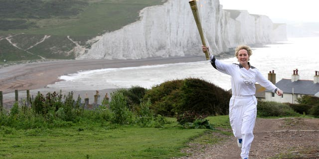 July 17, 2012: This image made available by LOCOG shows Kathy Gore, running with the Olympic Flame at Seaford Head, with a view of the Seven Sisters cliffs, southern England.