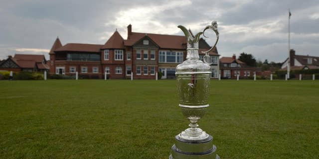 """The British Open Golf trophy the """"Claret Jug"""" is displayed  by the clubhouse at the Royal Liverpool Golf Club before the British Open golf championships, Hoylake, England, Wednesday, April 22, 2014.  The tournament begins on Thursday July 17, 2014. (AP Photo/Jon Super)"""