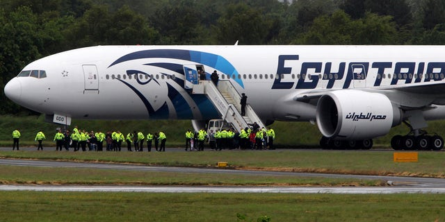 June 15, 2013: Passengers leave the Egyptair aircraft at  Prestwick Airport, Scotland,   after it was diverted while en route from Cairo to New York.  It is reported that BBC employee Nada Tafik, who was on board the plane, said she found a note in a toilet apparently threatening to start a fire.
