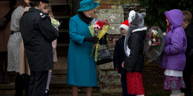 Britain's Queen Elizabeth II smiles as she receives flowers from children after attending the traditional Christmas Day church service in Sandringham, Inghilterra.