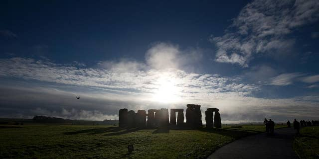 FILE - In this Tuesday, Dec. 17, 2013 file photo, visitors take photographs of the world heritage site of Stonehenge, England.