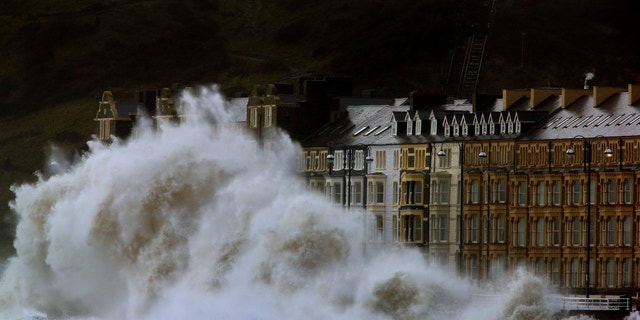 Waves crash against the Aberystwyth coastline in Wales, as strong winds and high tides continue to blow in from the west.