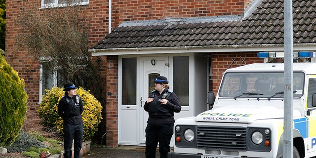 In this Tuesday, March 6, 2018 file photo, police officers stand outside the house of former Russian double agent Sergei Skripal in Salisbury, England. British police say they believe a Russian ex-spy and his daughter first came into contact with a military-grade nerve agent at their front door.