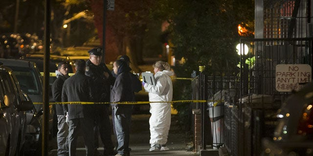 October 27, 2013: Police officers wait outside a residence in the Sunset Park neighborhood of Brooklyn where five people, including a toddler, were stabbed to death earlier in New York. (AP Photo)