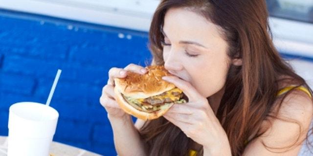 Beautiful young lady eating a tasty burger at an outdoor cafe. Horizontal Shot.
