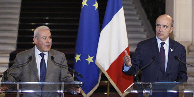 November 23, 2011: French Foreign Minister Alain Juppe, right, and Burhan Ghalioun, the head of the Syrian National Council opposition group addresses reporters during a news conference following their meeting in Paris.