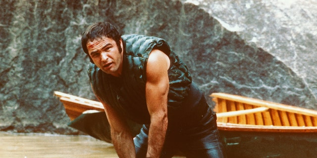 Burt Reynolds, US actor, holding onto some rocks as he struggles in the water with his boat behind him in a publicity still issued for the film, 'Deliverance', USA. The 1972 thriller, directed by John Boorman, starred Reynolds as Lewis Medlock.