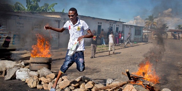 May 14, 2015: A civilian jumps over a burning barricade of rocks erected by residents to protect themselves from police in a northern district of  Bujumbura, the capital of Burundi. (AP Photo/Erik Esbjornsson)