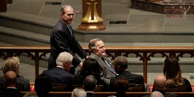 Former President George W. Bush pushes his father former President George H.W. Bush at former first lady Barbara Bush's funeral.