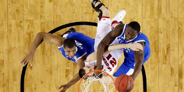 CORRECTS WISCONSIN PLAYER TO JOSH GASSER, INSTEAD OF TRAEVON JACKSON - Wisconsin guard Josh Gasser is caught between Kentucky guard Aaron Harrison (2) and forward Julius Randle (30) during the first half of the NCAA Final Four tournament college basketball semifinal game Saturday, April 5, 2014, in Arlington, Texas. (AP Photo/David J. Phillip)
