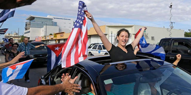 File- In this Nov. 26, 2016, file photo, Cuban-Americans react to the death of Fidel Castro, Saturday, Nov. 26, 2016, in the Little Havana area in Miami. For the hundreds of thousands of children born of Cuban exiles, some who are two and three generations removed from the island, Fidel Castros death potentially opens a door to a world previously off-limits. (AP Photo/Alan Diaz, File)