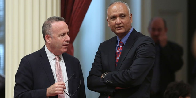 Senate President Pro Tem Darrell Steinberg, D-Sacramento, left, talks with Sen. Ed Hernandez, D-Covina at the Capitol in Sacramento, Calif., Monday, April 21, 2014. Hernandez proposed a constitutional amendment that would ask voters to again allow public colleges to use race and ethnicity when considering college applicants.  The proposal stalled this year after backlash from Asian Americans.(AP Photo/Rich Pedroncelli)