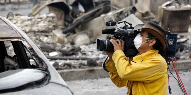 A video operator uses a mask as protection against smoke and ash while filming the remains of an apartment building lost in a wildfire two days earlier, Sept. 14, 2015, in Middletown, Calif.