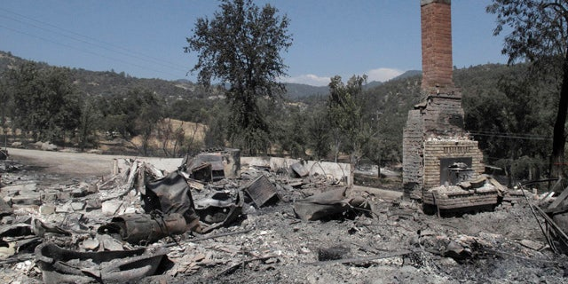 August 19, 2014: A chimney stands amid the remains of a burnt structure near Oakhurst, Calif. (AP Photo/Scott Smith)