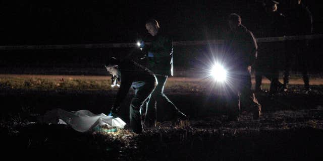 Dec. 9, 2011:nvestigators examine a crime scene along the Charles River in Boston.