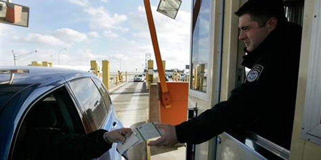 Jan. 31, 2008: A U.S. Customs officer hands back a Michigan drivers license and information pamphlet to a driver arriving from Canada at the Ambassador Bridge in Detroit.