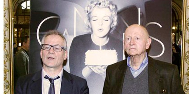 April 19, 2012: President of the Cannes Film Festival Gilles Jacob, left, and artistic Director Thierry Fremaux, pose in front of the Cannes International Film Festival poster for the upcoming 65th edition of the festival featuring US actress Marilyn Monroe during a press conference to announce this years festival line up in Paris.
