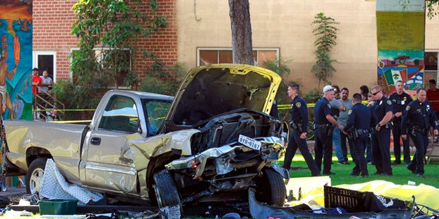 Police stand near the pickup truck that landed at Chicano Park in San Diego on Saturday, Oct. 15, 2016.