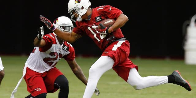 Arizona Cardinals' Michael Floyd, right, makes a catch in front of Tony Jefferson during the first day of NFL football training camp on Saturday, July 26, 2014, in Glendale, Ariz. (AP Photo/Ross D. Franklin)