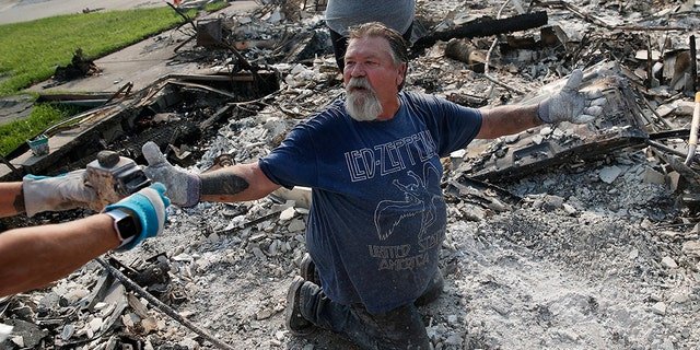 Rick Kincaid reacting as his wife Melodie Kincaid, left, finds his childhood toy as they sift through the charred remains of their home burned in the Carr Fire on Saturday in Redding.