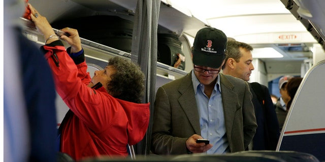 FILE - In this Thursday, Oct. 31, 2013 file photo, a passenger checks his cell phone while boarding a flight,  in Boston.  Allowing airline passengers to make cellphone calls in-flight is asking for trouble, lawmakers said Tuesday, Feb. 11, 2014, as a House panel approved a bill to ban such calls. (AP Photo/Matt Slocum)