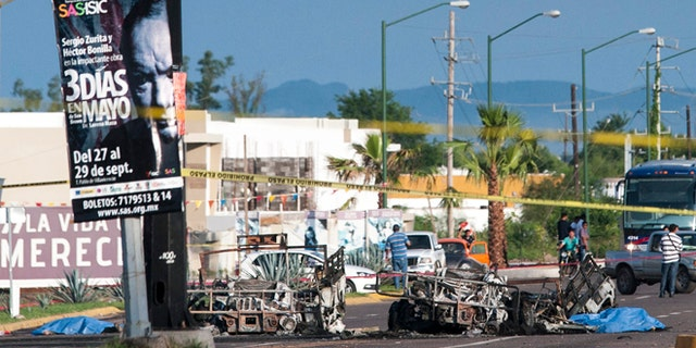 Police investigators examine the site where a military convoy was ambushed with grenades and high-powered guns, killing five soldiers in the city of Culiacan, Mexico, Friday, Sept. 30, 2016. Local military commander Gen. Alfonso Duarte said it is very probable that the attack was carried out by the sons of imprisoned drug lord Joaquin ââ¬ÅEl Chapoââ¬Â Guzman. (AP Photo/Hector Parra)