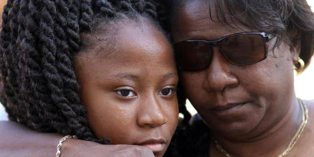 Antonee Martin, left, and her mother Latrechia Jackson, right, visit the memorial site set up in front of the Emanuel AME Churchin June, 2015, after Martin's aunt Susie Jackson was killed.