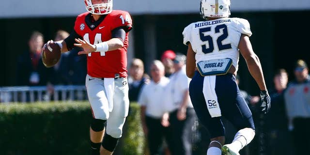 Georgia quarterback Hutson Mason (14) throws under pressure from Charleston Southern linebacker Gabe Middlebrook (52) in the first half of an NCAA college football game, Saturday, Nov. 22, 2014, in Athens, Ga. (AP Photo/John Bazemore)