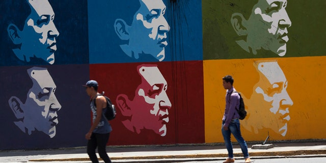 Two men skate board past a mural of Venezuela's late President Hugo Chavez in downtown Caracas, Venezuela, Tuesday, March 4, 2014. Hes been dead a year, but Chavezs face and voice are everywhere. On Wednesday, the country will mark Chavez's death, who died at age 58 on March 5, 2013. (AP Photo/Rodrigo Abd)