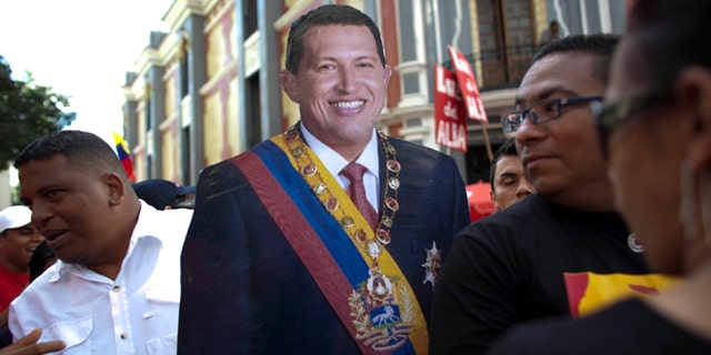 Jan. 10, 2013: In this file photo, supporters of Venezuela's President Hugo Chavez carry a life-size cut out image of him during a symbolic inauguration ceremony for Chavez, who was in Cuba for cancer treatment at the time, in Caracas, Venezuela.