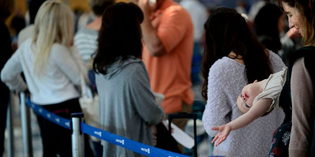September 26, 2014: Ann Walden and her 15 month-old daughter Delphine wait in line after their flight to Baton Rouge was delayed at O'Hare International Airport in Chicago. All flights in and out of Chicago's two airports were halted Friday after a fire at a suburban air traffic control facility sent delays and cancellations rippling through the U.S. air travel network. (AP Photo/Paul Beaty)