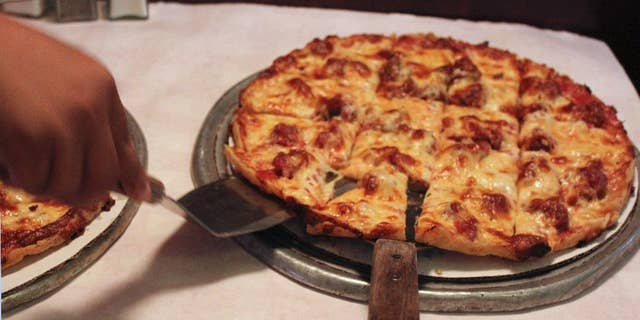 Sept. 5, 2014l  A waitress serves a cheese and sausage pizza to participants on a pizza tour at Pizano's in Chicago.