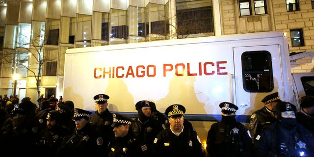 CHICAGO, IL - DECEMBER 18 : Chicago police officers surround a police vehicle as they watch demonstrators protesting the fatal police shooting of Laquan McDonald December 18, 2015 in Chicago, Illinois. Former Chicago police officer Jason Van Dyke, who was charged with murder last month in the shooting death of 17-year-old McDonald last year, was indicted on six counts of first-degree murder and one count of official misconduct earlier this week. (Photo by Joshua Lott/Getty Images)